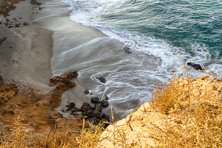 sandstone path overlooking cliff side, pacfic ocean waves on a sandy beach, rocks Stock Photo