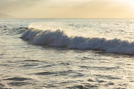 grayed wave with foam and backwash against light blue ocean expanse Foto de archivo