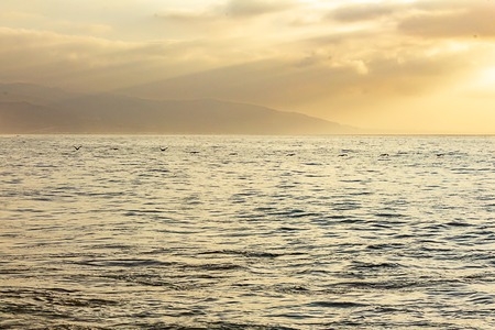 open ocean expanse at sunrise, with clouds, sunrays, water texture, and distant hills,
