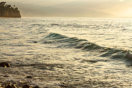 ocean swell forming into a wave on green and blue glowing ocean expanse Archivio Fotografico