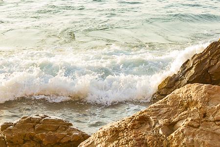 foaming wave breaking onto textured boulders at shoreline Foto de archivo