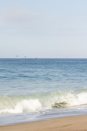 kleine Welle bricht an sandiger Küste und offenem Ozean in Kalifornien