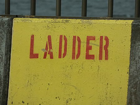 bright yellow sign showing escape ladder placement near overpass Foto de archivo - 124702651