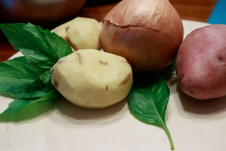 peeled and whole red potatoes with basil and onion