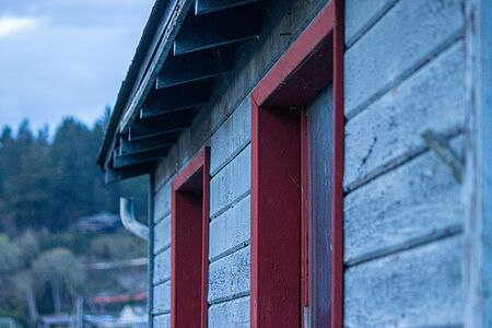 blue wooden siding and red trimmed windows aged and distressed from time and weather Stock Photo