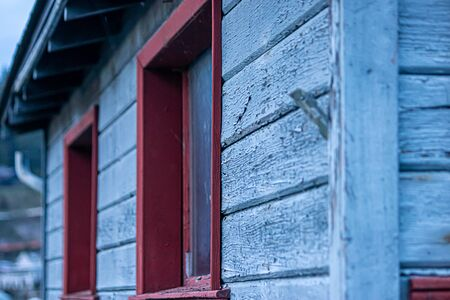 old building with blue wooden siding and red trimmed windows aged and distressed from time and weather