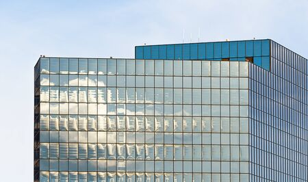 closeup of high rise building glass sides in square pattern, reflectiong the sunlight Imagens