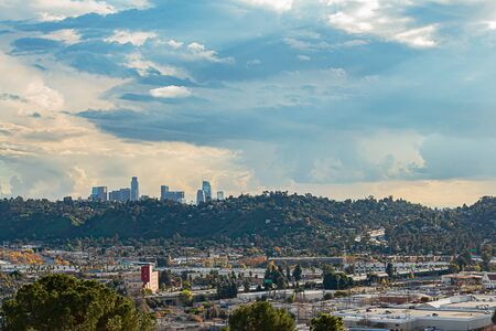 panaramic view of city businesses and homes with hillside homes and downtown LA towers in the distance Imagens