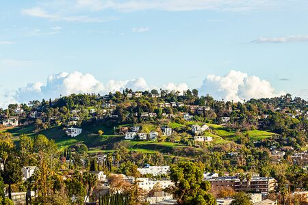 green grassy hillsides in autumn with palm and trees with homes with blue sky and clouds Imagens