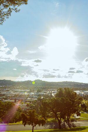 Sonneneruption über Panoramablick auf die Stadt mit Hügeln und Bäumen, Häusern, Unternehmen