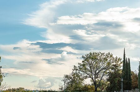 hillside view of panaramic sky and cloudscape, lamp post and bench Imagens