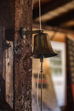 antique bell hanging from old wooden beams Imagens