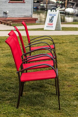 red stackable chairs in a row on grass during summer park show