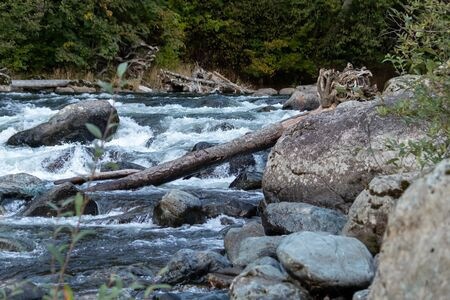 large boulders sticking out of rapids on a blue river 写真素材
