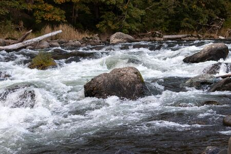 White river rapids in a deep blue river running over rocks 写真素材