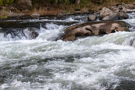 white water rapids in a deep blue river 写真素材