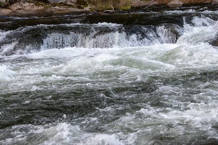 small white water fall into rapids on blue river