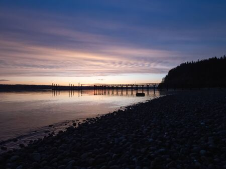 sunset glowing over a dock leading out to water of puget sound in summer afternoon Stock Photo