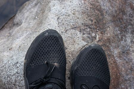 front tips of black shoes standing on boulder