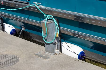 green roap tied down to dock area near a saltwater marina Banque d'images