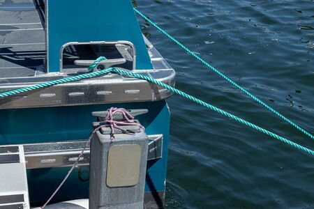 green roap tied down to dock area near a saltwater marina in sunlight Banque d'images
