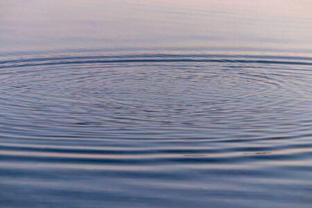 increspature dell'acqua causate da pietre lanciate sull'acqua al tramonto