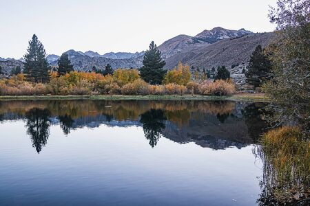 reflecctive mountain lake with pines aspens grass and mountain colors Stock Photo