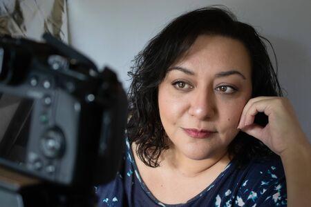 mature woman influencer runs buisness over social media with camera