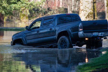 a big truck driving through a flood Reklamní fotografie