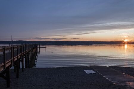 sun setting over a long fishing dock 免版税图像