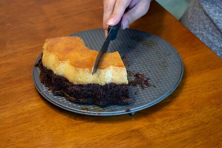 careful hands cutting into a chocolate and custard cake on a metal serving dish 免版税图像