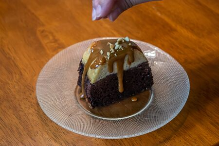 sprinkling nut topping over chocolate cake covered in caramel sauce