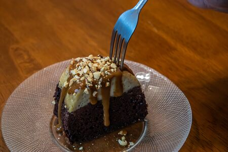 a fork taking a bite out of a slice of chocolate cake with caramel and nuts on top 免版税图像