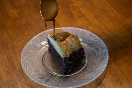 drissling caramel de leche over a chocolate and custard cake slice