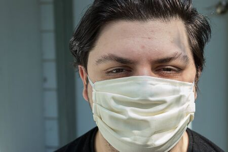 young man with dark hair in face mask for protection