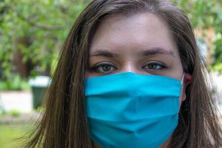 young woman with dark hair in face mask for protection