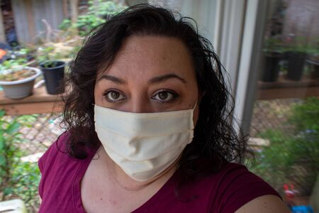 mature woman with dark hair in face mask for protection