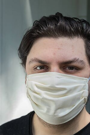 young man with dark hair wearing protective face mask