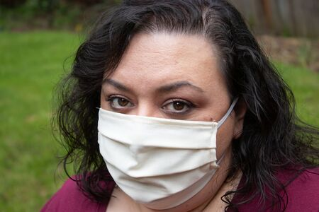 mature woman with dark hair wearing protective face mask