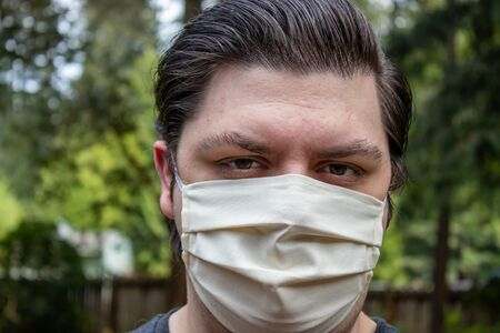 young man with dark hair in face mask for protection outside