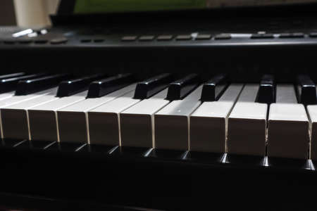 keys of a piano in dark shadow and bright light