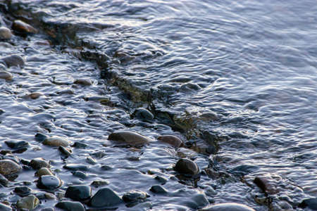small waves flowing in over rocky shoreline