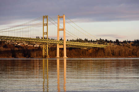 Tacoma Narrows Bridge in sunset lighting under clouds