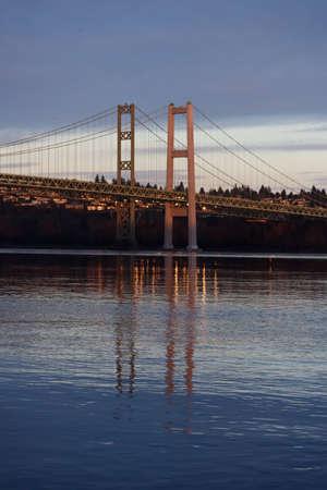 calm water reflecting narrows bridge and sky at dusk Stock fotó