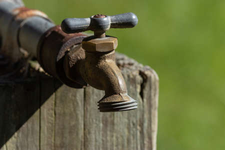 old metal water tap bolted onto a wooden post