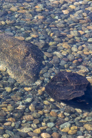 rocks of various sizes and colors under shallow water Фото со стока