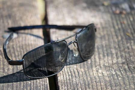 black sunglasses sitting on a bench in the sun Фото со стока