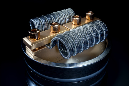 Vaping atomizer with clapton coil. Black background