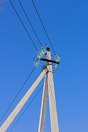 insulators: Electric power lines mounted on insulators and a tall concrete power pole