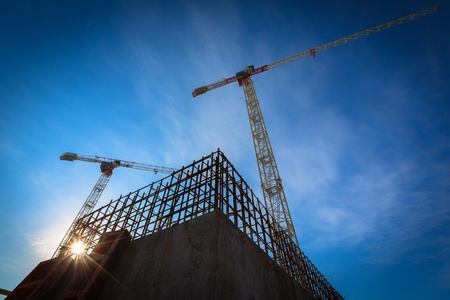 industrial district: Construction site with cranes on sky background Editorial